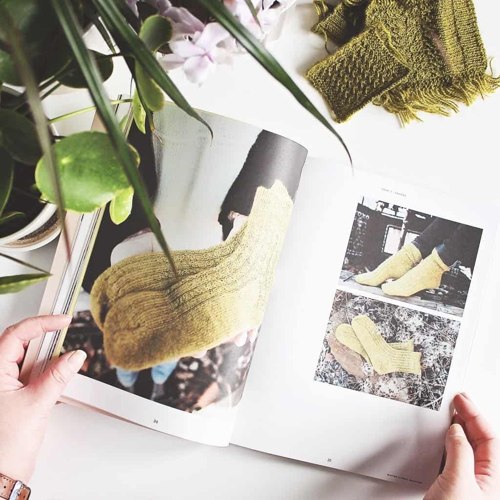 Hands holding open a magazine, showing a pair of socks on the pages