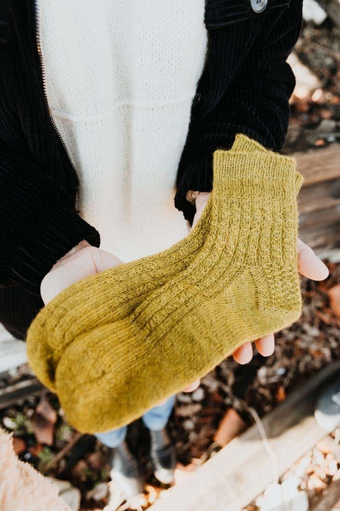 A pair of hands holding hand knit Tidal Socks made of wool