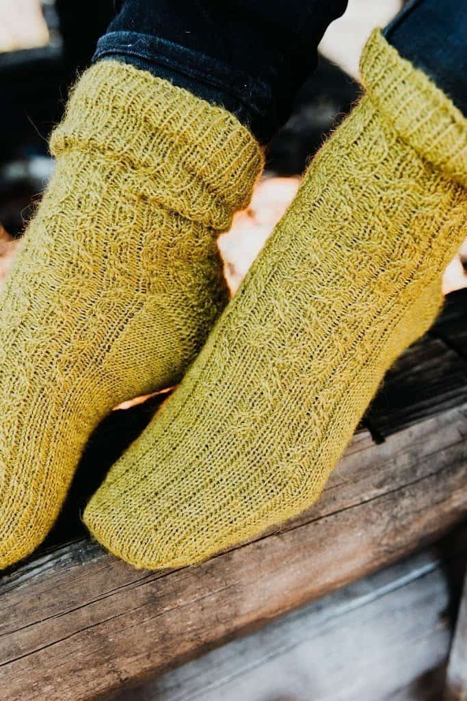 A close up of feet modelling a pair of hand knit Tidal socks