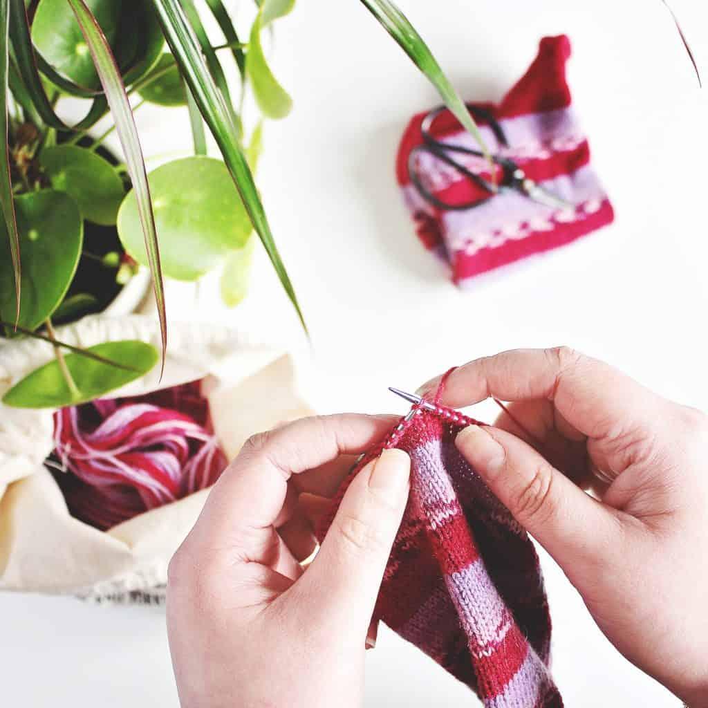 Hands knitting red wool socks