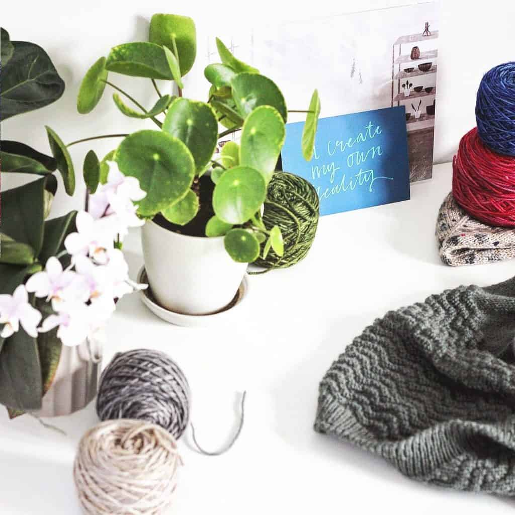 A pile of knitting and balls of yarn on a white table with houseplants and orchids