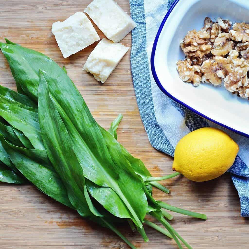 flat lay wild garlic pesto ingredients on a wooden chopping board