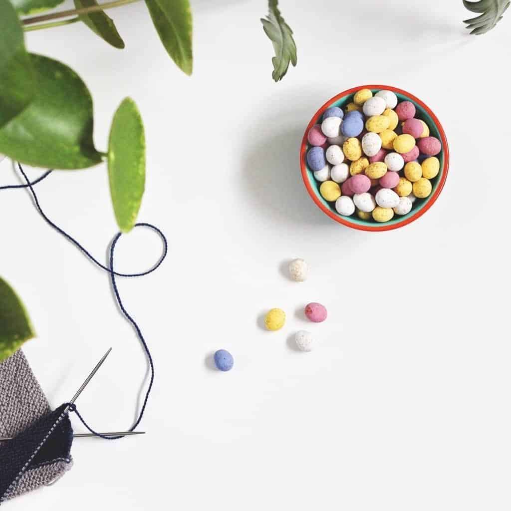 a bowl of tiny pastel coloured chocolate eggs on a white table
