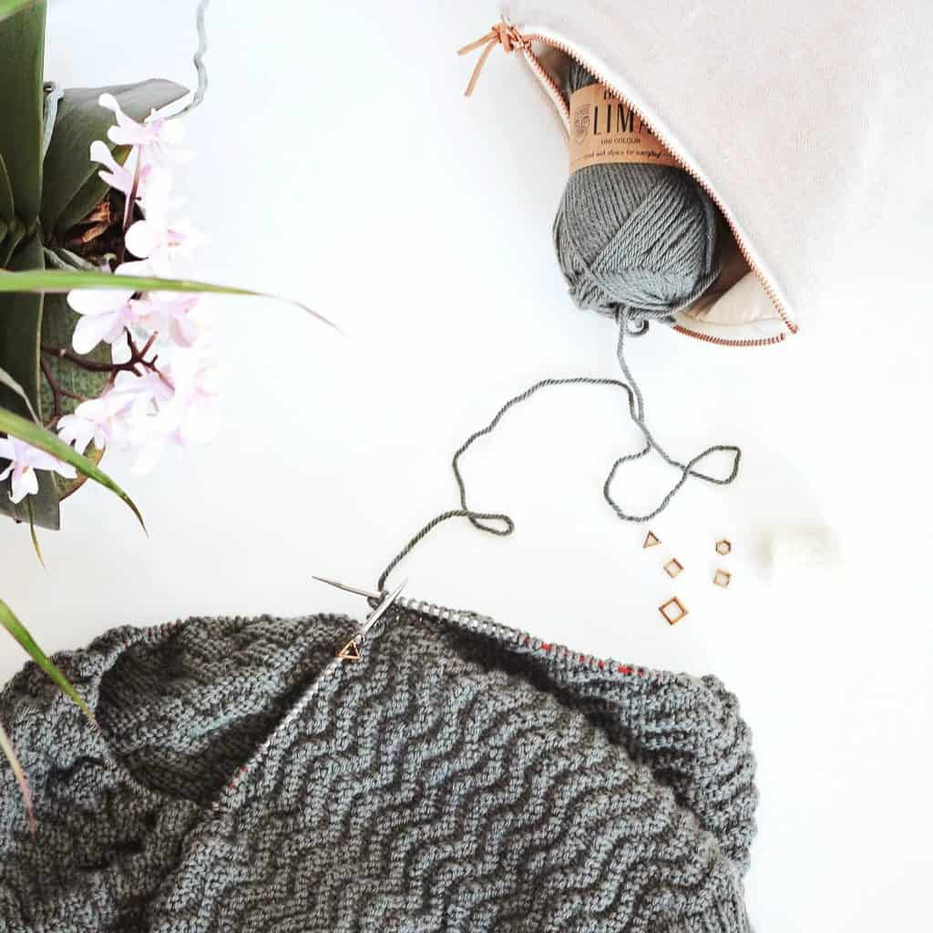 knitting on a white table, a project bag with a ball of yarn peeking out of it and orchids