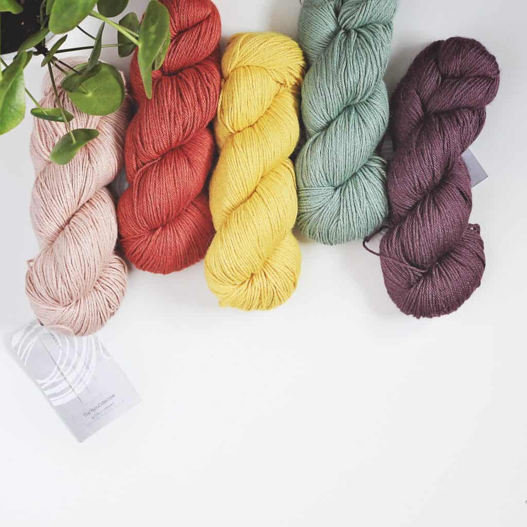 Five skeins of The Yarn Collective Rivoli Sport on a white table